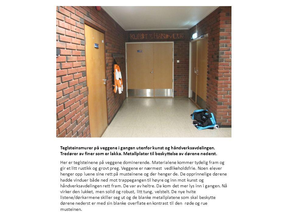 Teglsteinsmurer på veggene i gangen utenfor kunst og håndverksavdelingen. Tredører av finer som er lakka. Metallplater til beskyttelse av dørene nederst.