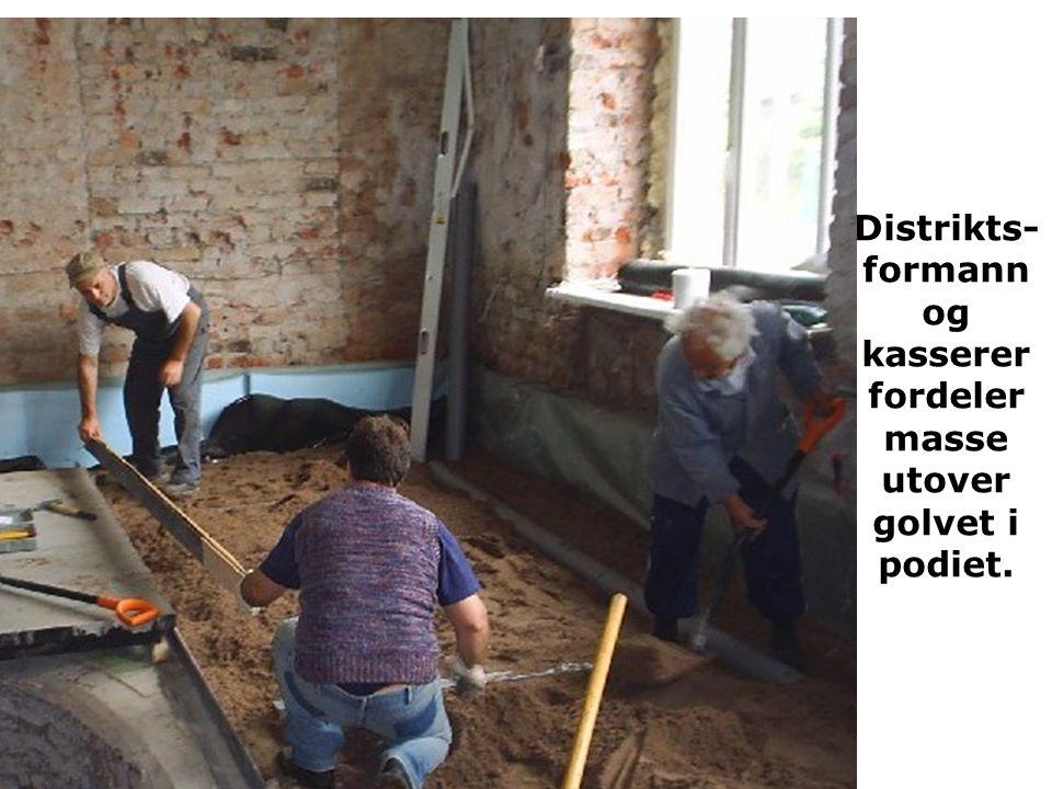 Distrikts-formann og kasserer fordeler masse utover golvet i podiet.