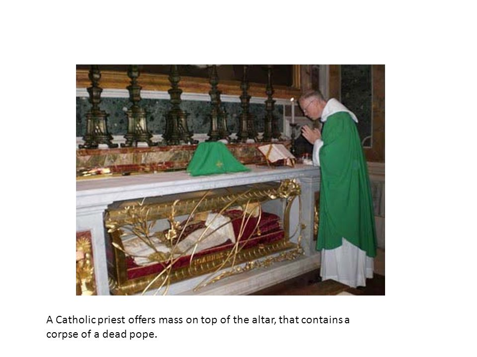 A Catholic priest offers mass on top of the altar, that contains a corpse of a dead pope.