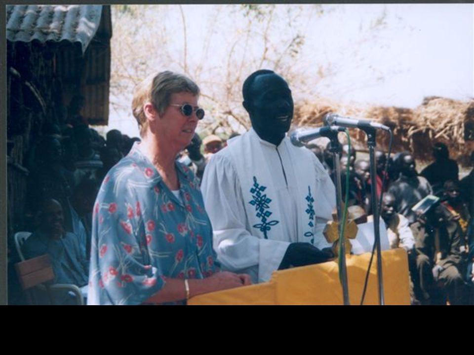 Feiring/gudstjeneste i forbindelse med innvielse av Det nye testamentet på Gumuz. Agallo Meti, Etiopia 15. februar 2004. Rundt 1500 mennesker deltok i feiringa. Dei fleste av disse var frå Blånildalen, og flertallet tilhørte trolig folkegruppa gumuz. Det var mange gjester fra inn- og utland. Her taler den norske ambassadøren, Mette Ravn på vegne av Norge.