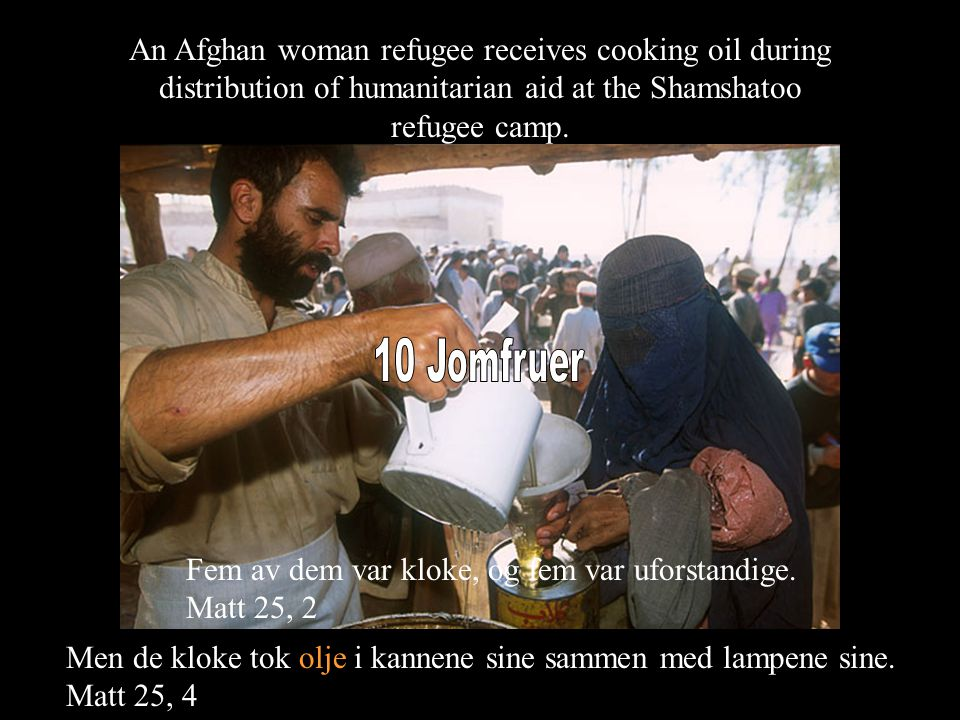 An Afghan woman refugee receives cooking oil during distribution of humanitarian aid at the Shamshatoo refugee camp.