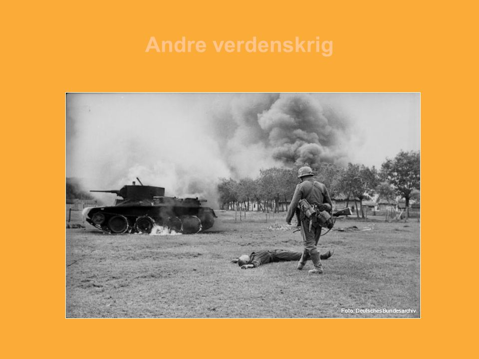 Andre verdenskrig Foto: Tysk soldat inspiserer en død sovjetisk soldat. En sovjetisk stridsvogn står i flammer.
